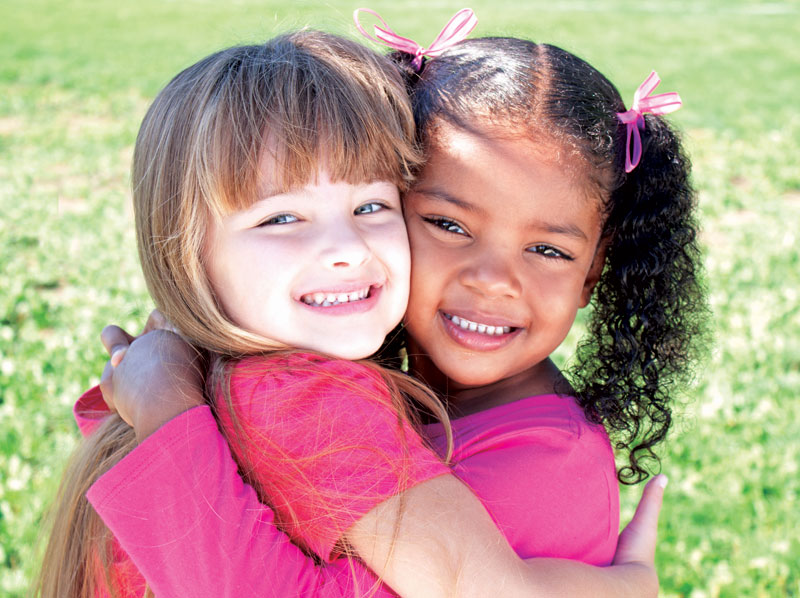 Two young girls hugging and smiling.